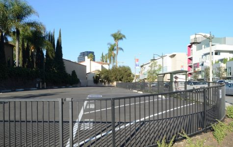 Student parking lot waits while pavement 'cures' behind new fence