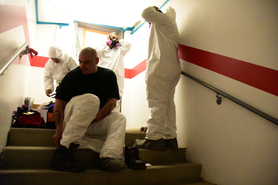 PROTECTION: Workers from 911 Restoration put on protective clothing before heading downstairs to the work area. According to Mr. Albert Garcia, those working in the area must wear protective clothing to avoid being exposed to any of the contaminants.