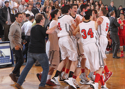 OVERJOYED: Varsity basketball team mobs center court, joined by Head of School Rabbi Segal and Agenda Chair Daniel Schwartz, sfter defeating Frisch Academy 62-53 at YU's Red Sarachek Tournament in New York. Firehawks are now top-ranked basketball team in national polls for the first time in school history