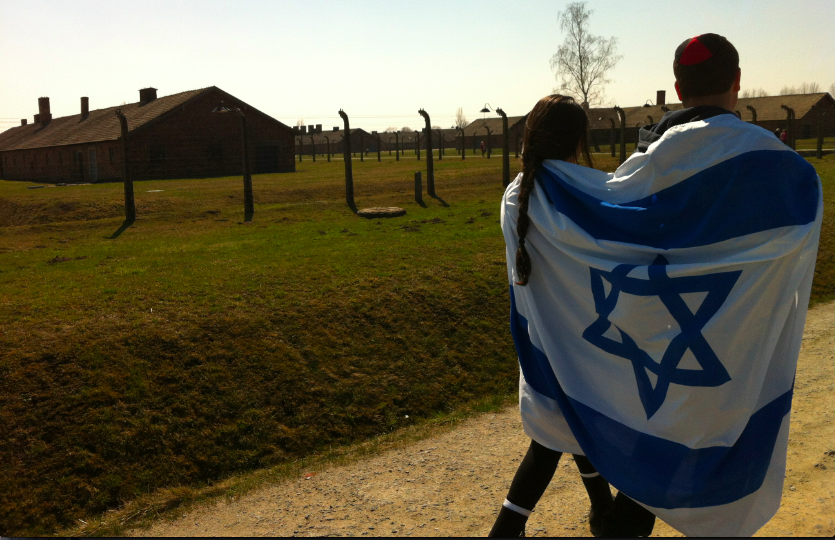 EXPERIENCE%3A++Members+of+the+class+of+2013+were+wrapped+in+the+Israeli+flag+at+Auschwitz+last+April+on+the+senior+Poland-Israel+trip.+The+endowment+will+hopefully+make+it+possible+for+more+seniors+to+attend+the+trip.