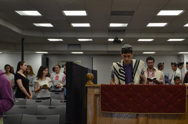 FOCUS: During Shacharit earlier this month, freshman Eric Bazak read the prayer for the sick as Reb Tuli Skaist looked on.  It was added earlier this year after parents of several students were diagnosed with serious illness.
