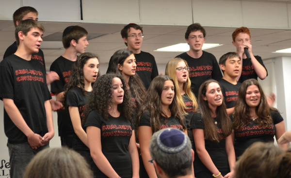 SPICE: Shalhevet's choir sang pop songs with beatboxing and even some choreography at its concert May 29.  Freshman Jake Benyowitz, at top right, provided the percussion.