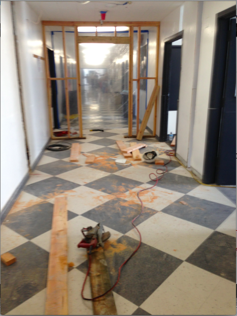 DIVIDER: Construction in the main hallway last week began to close off the north end of the building, planned for demolition to make way for a new three-story campus. Demolition of the unused part of the building may begin next month.