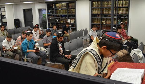 EARLY: It's not quite light out as sophomore Joseph Schnitzer leads Shacharit at the Hashkama Minyan, which starts at 7:25 a.m. in the Beit Midrash.