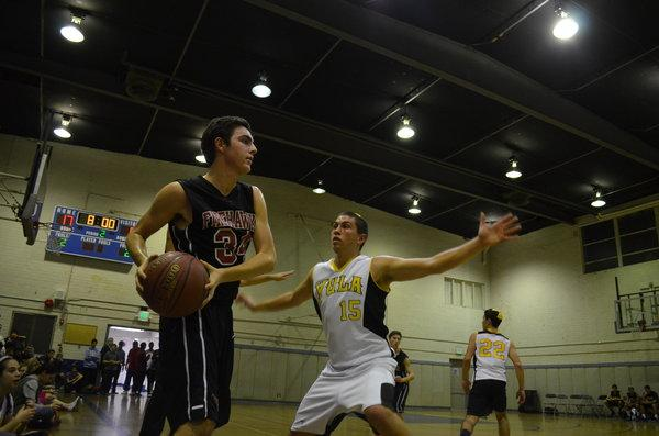 INBOUND: Sophomore Jacob Dauer tries to inbound the basketball against Ariel Sokol of YULA in the annual rivalry game. The girls' team played before the boys and won 59-40, while the boys lost 62-36.