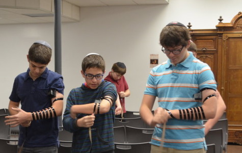 BOYS: Freshmen Zev Kent, Ezra Fax and Isaac Goor put on their tefillin at Shacharit.
