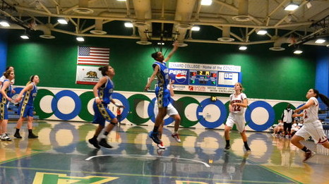SHOOT: Lady Firehawks watch a shot bounce off the rim as Lions' center Simone Swain (No. 12) controls the paint.