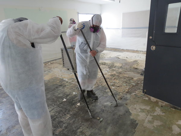 DANGER: Workers remove asbestos, a toxic chemical that was formerly used to prevent fires, from the walls of the old school building April 29.  Asbestos must be removed first to prevent poison dust from being released when the building is demolished.