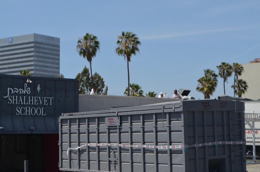 HAZ-MAT: Visible above a specially covered dumpster, workers on the roof removed lead and asbestos May 12.