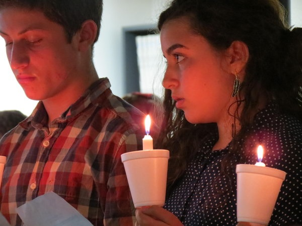 MEMORIAL: Freshmen Nathan Benyowitz and Tania Bohbot read names of child victims at ceremony in Beit Midrash.