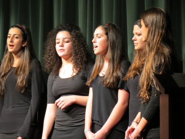 HARMONY:  Natalie Dahan, second from left, beat-boxed as Shirel Benji, Liat Bainvoll, Talya Joffe and Nicole Soussana sang during the female Choirhawks performance April 30.  YULA's choir, right, was entirely student-led.