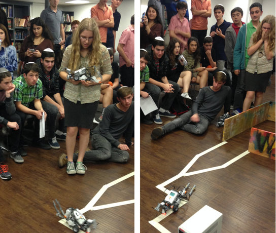 TENSION: Members of CIJE, the afterschool science and technology class, watch their robots follow a taped path in Town Hall Dec. 19. Though they were programed to do so, none of the robots succesfully picked up the box at the end of the course.