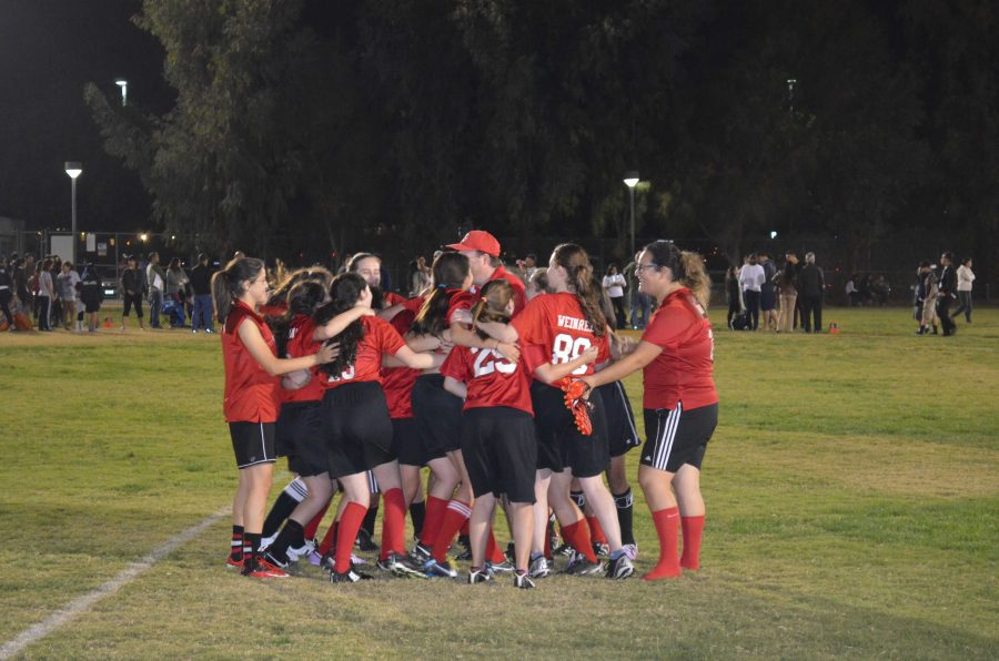 Girls+flag+football+team+surrounds+coach+Buckley+for+a+pre-+game+speech+at+the+2014+Loma+Linda+Tournament.%0A