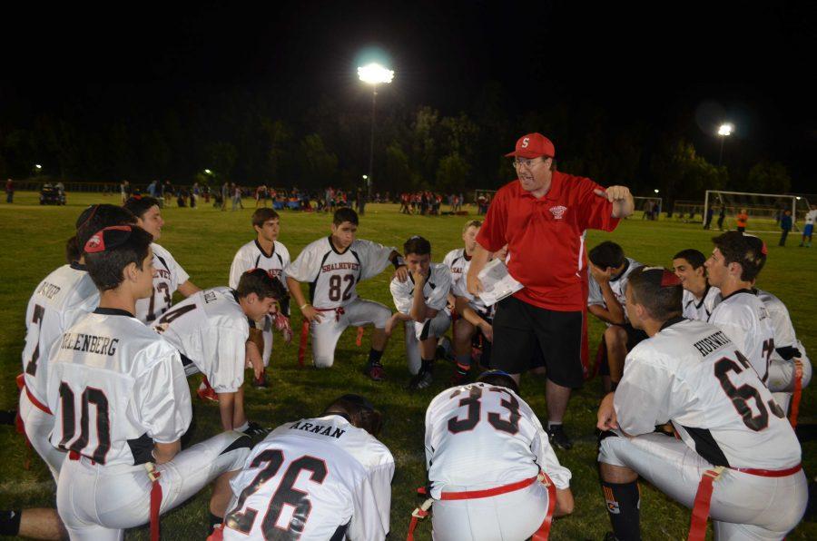 Boys flag football team listens to the coach on one knee during half time Nov. 4.