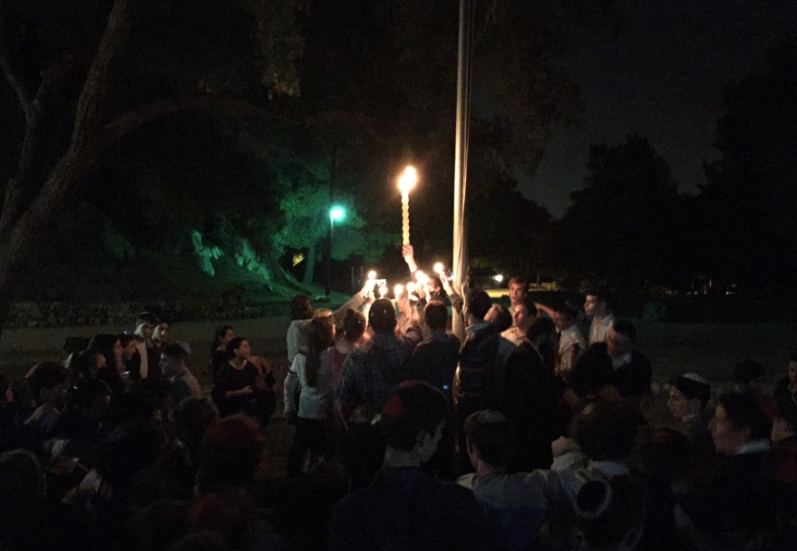 FLAME: Seniors held candles during Havdalah at the school Shabbaton Nov. 14 at Camp Max Strauss in Glendale.