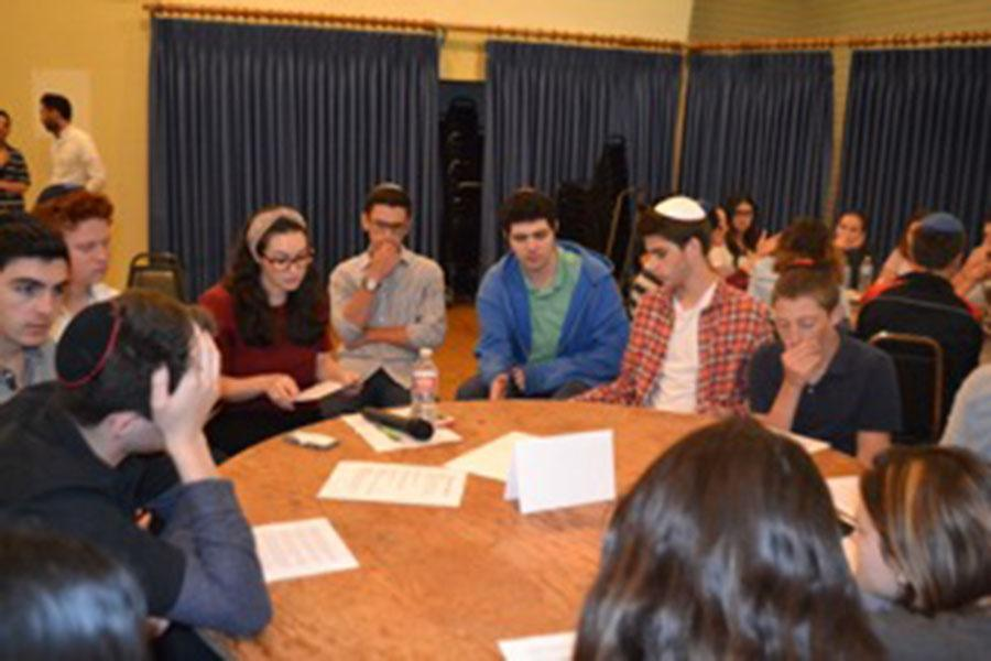 MESSAGE: Students and Judaic Studies teacher Mrs. Ruthie Skaist, fourth from left, together  analyzed a poem written by a Holocaust survivor.