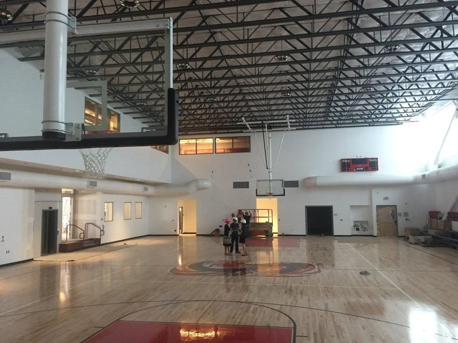 INDOOR+GYM%3A+State-of-the-art+gym+has+a+regulation+basketball+court+and+volleyball+court%2C+along+with+pulldown+bleachers+along+the+right-side+wall+and+natural+light+pouring+in+from+windows+as+long+as+the+room.++A+new+Firehawk+logo+is+on+the+floor+at+center+court.+