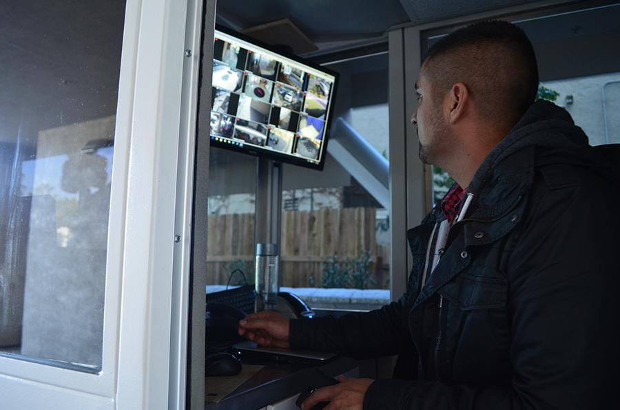 WATCHFUL: Manny Fernandez, Director of Security, monitoring cameras from the gate-control booth in the driveway.  Below, the front gate of the school extends to driveway roof and cannot be climbed.