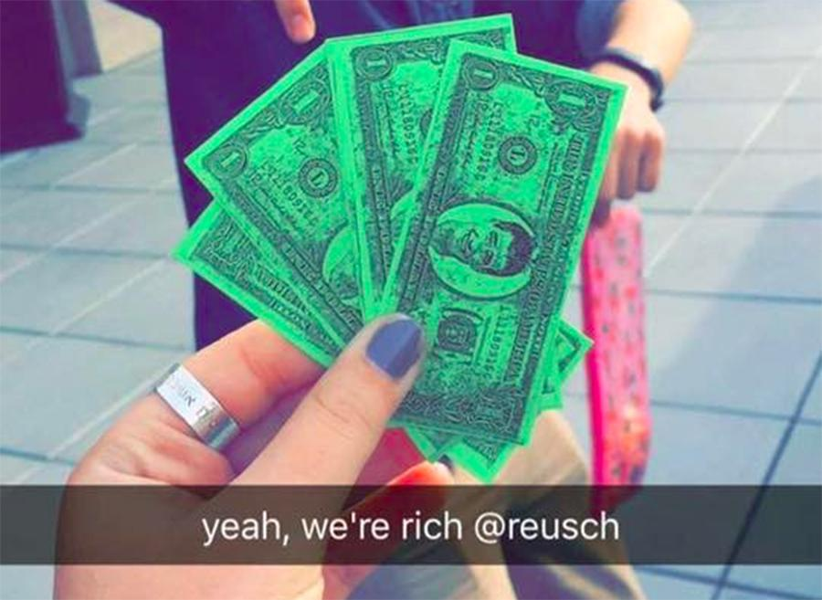 UNEVEN: Junior Sarit Ashkenazi admires her Reuschbucks on Snapchat last month. Students worked toward the same goal, but some started with only a few dollars while others were given many.