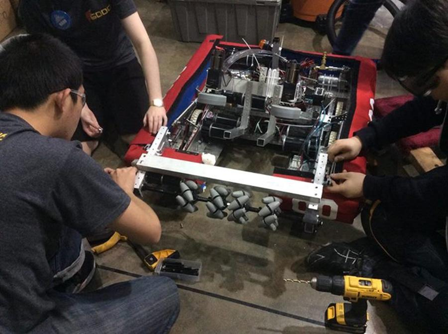 Team members perform small fixes on the robot in preparation for an FRC match. The team won 6 of 8 matches.