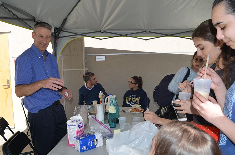 OPEN: Dr. Amit served coffee to students in an open sided tent on the rooftop turf during his two-week residency in February.