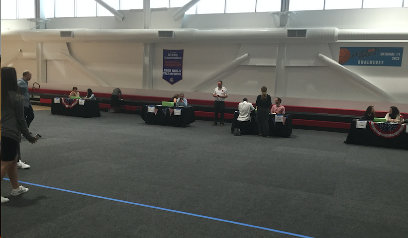 ORDERLY: Four voting stations were set up in the gym, one for each grade, overseen by teachers. People waited their turn in lines behind a blue line.