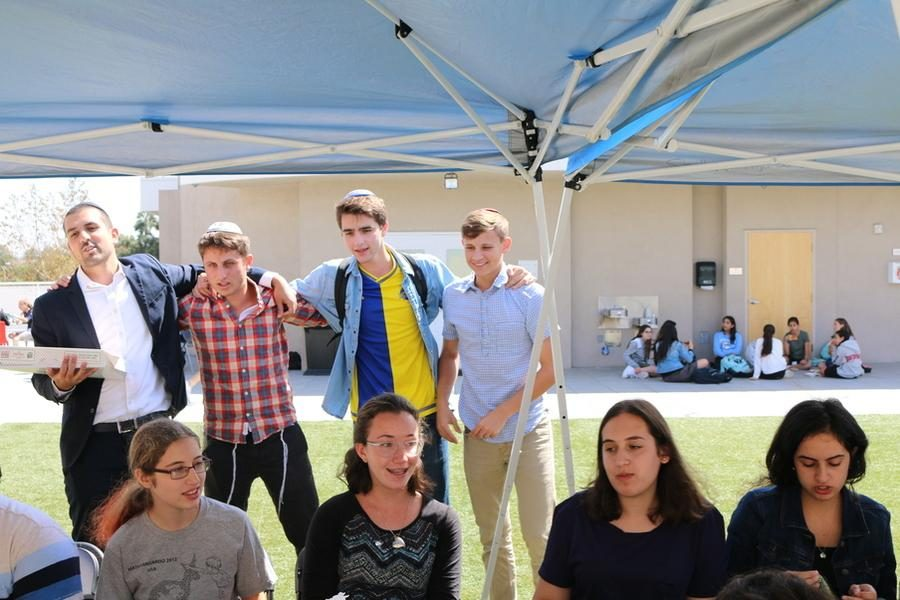 SPIRIT%3A+Students+from+all+grades+spend+Friday+lunchtime+singing+under+the+%27rakez%27+tent+on+the+roof%2C+led+by+Rabbi+Tsaidi%2C+at+left%2C+and+Rabbi+Block.