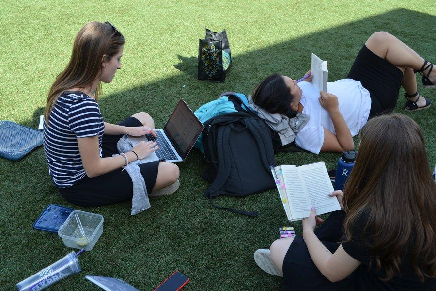 Concentration: Three seniors do their homework up on the turf.