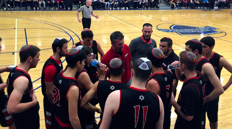 CONFER: FIrehawk players  met with Coach Ryan Coleman during the championship game at the Red Sarachek Tournament March 6 at Yeshiva University.