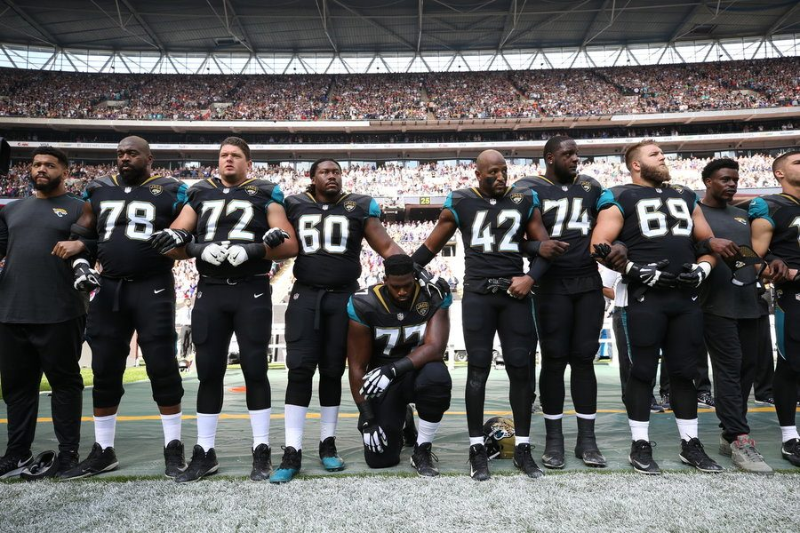 UNITY: Members of the NFL Jacksonville Jaguars locked arms as one player knelt during the National Anthem before their game against the Baltimore Ravens Sept. 24.