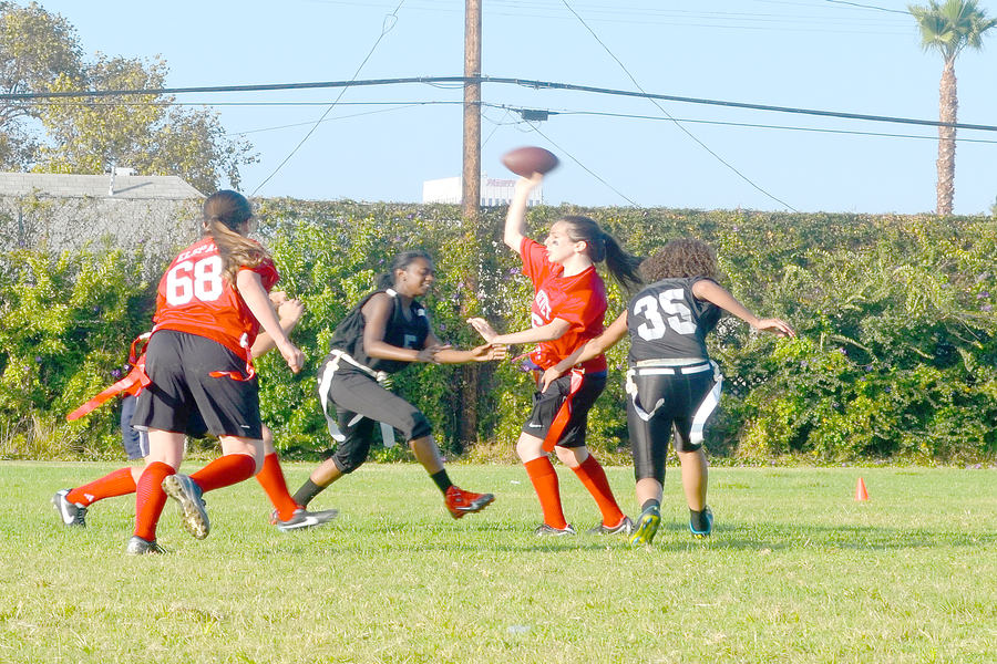 HISTORY: Firehawk quarterback Nicole Feder raised the ball over the players from LA Adventist High School in Sept. 2013. LA Adventist closed its athletic program this year, possibly ending Shalhevet's season.