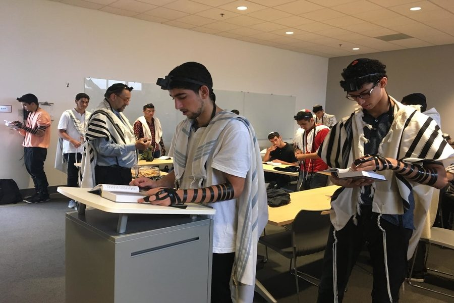 LEADING: Senior Benny Zaghi who started the Sephardic Minyan has help leading it from his classmate Ilan Bouskila (right), Rabbi Bouskila -- Ilan's father (left), and juniors Isaac Kahtan and Sam Navon.