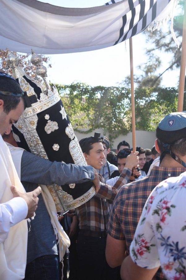 SCROLL: Adam Ritz helped carry a tallit as the new Sephardic Torah was paraded around the parking lot in its case, called a tik.