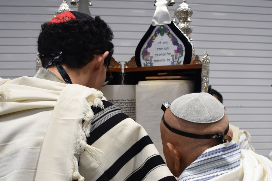 SCROLL: Senior Ilan Bouskila was first to chant from the scroll. Sephardic Torahs are read standing vertically, while Ashkenazic Torahs are read lying flat on the table.