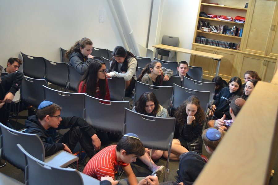 HIDING: Students crouch between chairs behind the mechitzah during Shalhevet's first-ever lockdown drill.