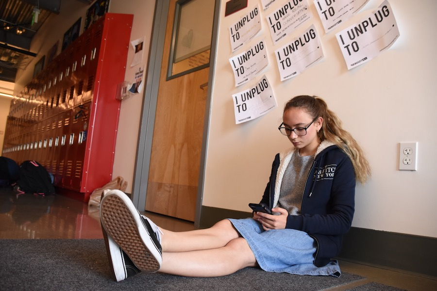 PHONE: Sophomore Shayna Schusterman shows social media is still alive and well in the second floor hallway. But some are opting in to get off of social media for while.