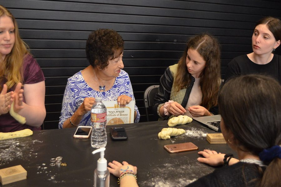 Ms. Karin, second to left, shares memories and stories of World War Two with students at her table braiding challah.