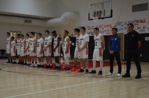 PAUSE:    Firehawk boys basketball team members paused on the court before the first game as Rabbi Block led 11 seconds of silence in honor of victims of the synagogue shooting in Pittsburgh.  Star guard Zack Muller, second from right in blue, did not play, but the Firehawks won anyway.