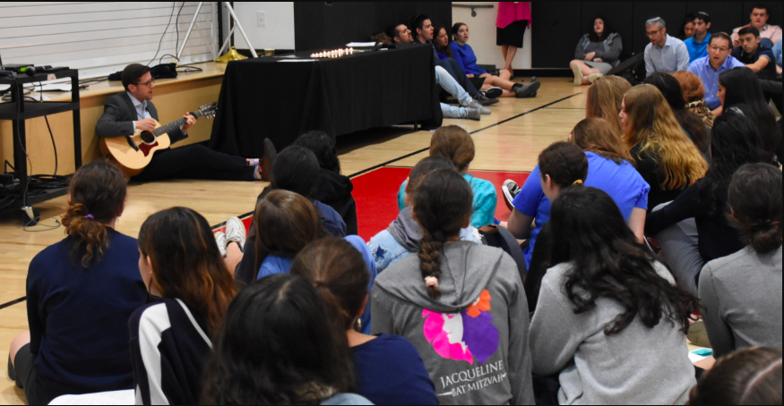 SONG: Rabbi David Block led the school in slow shira Oct. 29 as the school gathered on the floor of the gym to remember victims of the synagogue shooting in Pittsburgh.  Earlier, students had lit 11 candles, one for each of the victims.