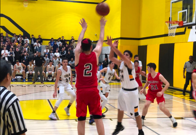 WINNERS:   No. 2 Ze'ev Remer aims for the basket during the close game between the Firehawks and the Panthers Dec. 20. At the end of the fourth quarter, it was Ze'ev who made the game-winning shot, from that same spot on the court.