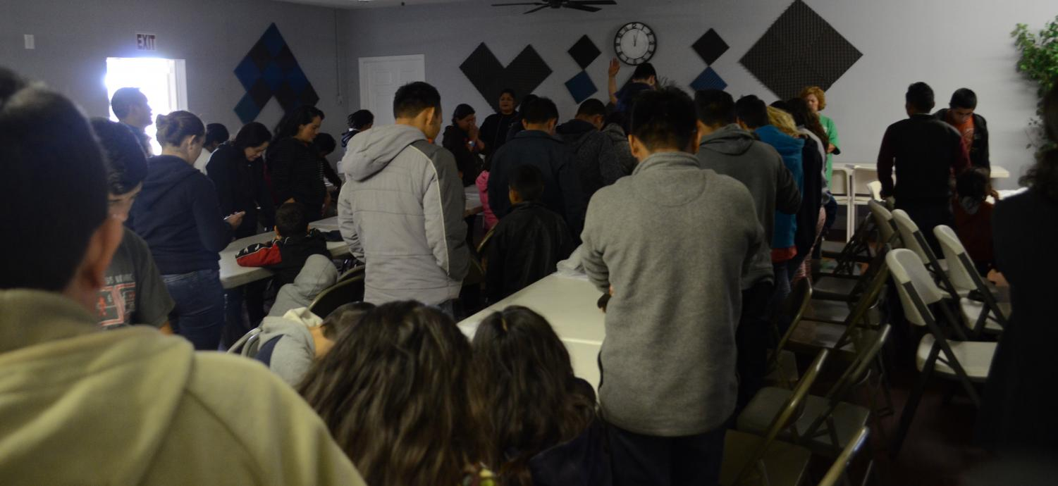 The+newly+arrived+families+bow+their+heads+in+a+prayer+led+by+Pastor+Ramon+Madrid+of+Casa+de+Oracion+No.+2+church.