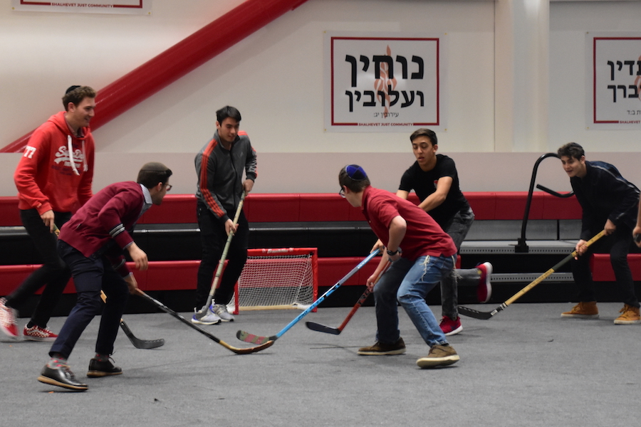 GAME:   Hockey club leader Adam Ritz shelters the ball during a scrimmage in the gym Jan. 30.  Photo by Carin Arbib