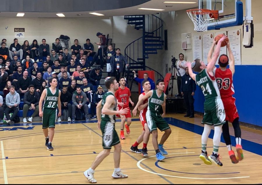 ATTACK: Firehawk forward and Sarachek MVP Asher Dauer goes for a lay-up as Wildcat junior A.J. Bennett tries to block it in the Firehawks' 60-41 win over the DRS Mar. 17. The Firehawks are the first team ever to win YU's Sarachek tournament two years in a row.