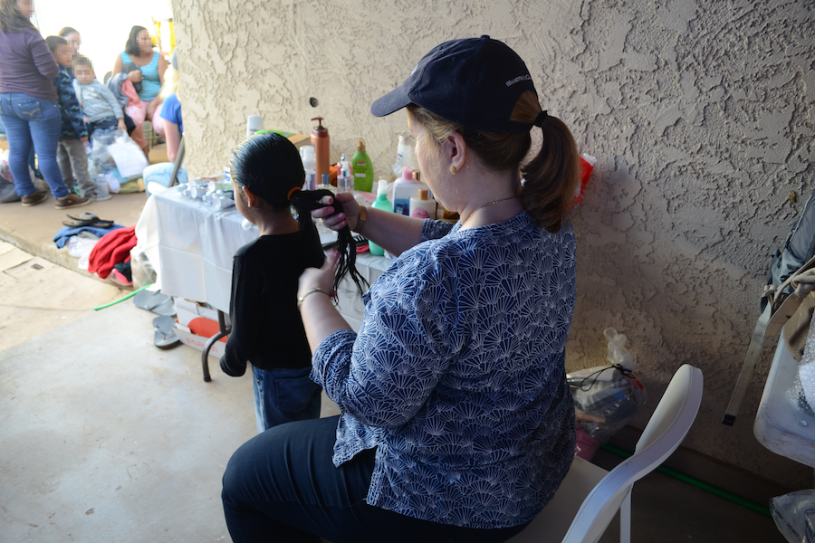 BRAID: Helped by volunteers from Los Angeles and elsewhere, asylum seekers who had been held in detention before being cleared to enter the U.S. were welcomed with their first showers and hot meals at the Casa de Oracion No. 2 church in northern Phoenix Jan. 16. Above, Marian Merritt braided one girl's hair.