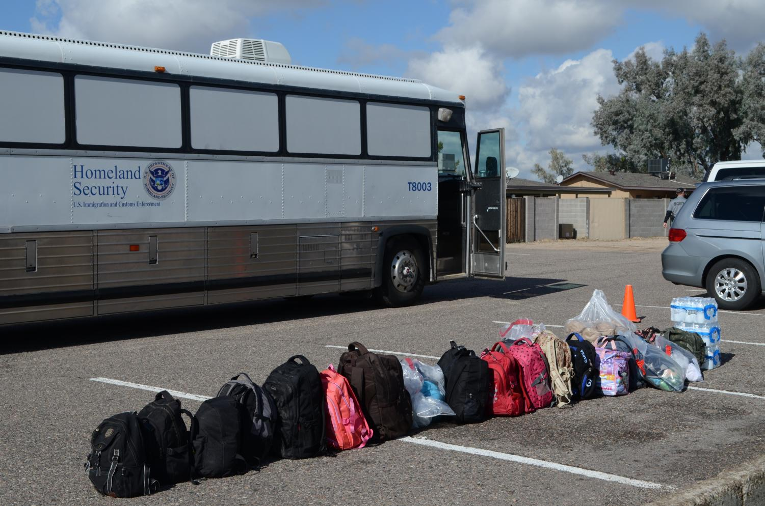 The+belongings+of+about+30+migrant+families+are+lined+up+in+the+church+parking+lot+after+being+taken+off+the+bus.+None+was+larger+than+a+backpack%2C+and+some+were+plastic+bags+provided+to+them+by+ICE.