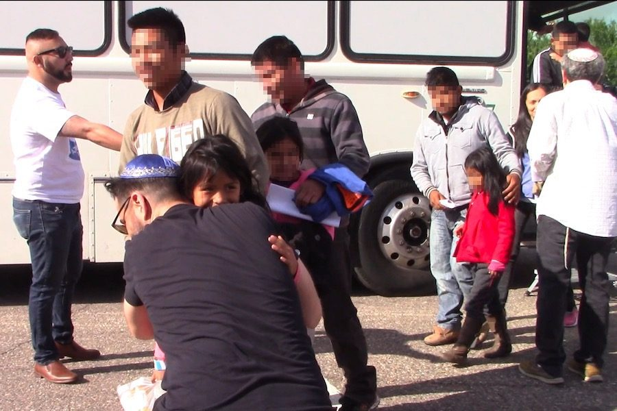 WELCOME: A young girl from Central America is welcomed by Shalhevet parent Mordechai Fishman after she stepped off the bus in Phoenix.