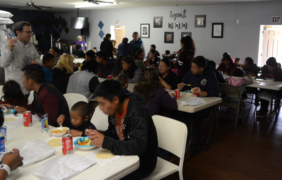 Migrant+families+are+served+a+tortillas%2C+hot+soup%2C+and+beverages%2C+by+volunteers+in+the+cafeteria.