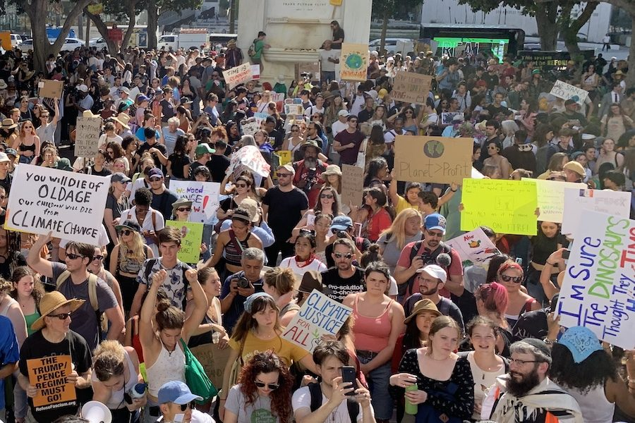 ORIGINAL:   About 2,000 protestors filled the streets of downtown Sept. 20, most under 30 and many carrying signs with slogans they'd painted themselves. They marched in hot weather from Pershing Square to City Hall, seen at top right behind palm trees against a blue sky.