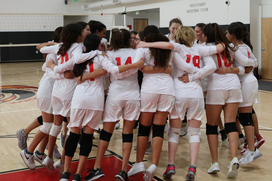 TEAMWORK%3A+Firehawk+volleyball+players+perform+a+team+cheer+ahead+of+their+home+game+against+Enviromental+Charter+on+Sept.+25.+Team+members+say+communication+is+important%2C+especially+among+players+who+call+for+the+ball.++Enthusiasm+for+the+sport+continues+to+grow+as+practice+becomes+more+rigorous.