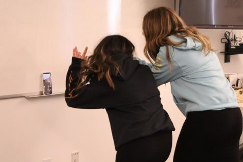 Sophomores Miriam Saedian and Audrey Gold film a TikTok dance in an empty classroom